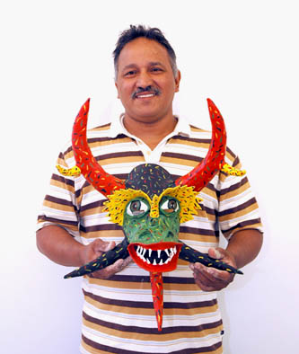 Angel Sánchez Ortiz holding one of his vejigante masks, Puerto Rican carnival  mask making, 2007; Holyoke, Massachusetts; Photography by Maggie Holtzberg