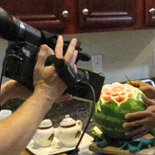 Phil Lupsiewicz filming Ruben Arroco at home; Carved fruit; 2013: Lowell, Massachusetts