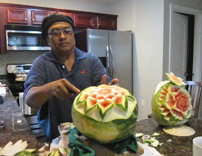 Ruben Arroco carving watermelon at home kitchen; Carved fruit; 2013: Lowell, Massachusetts